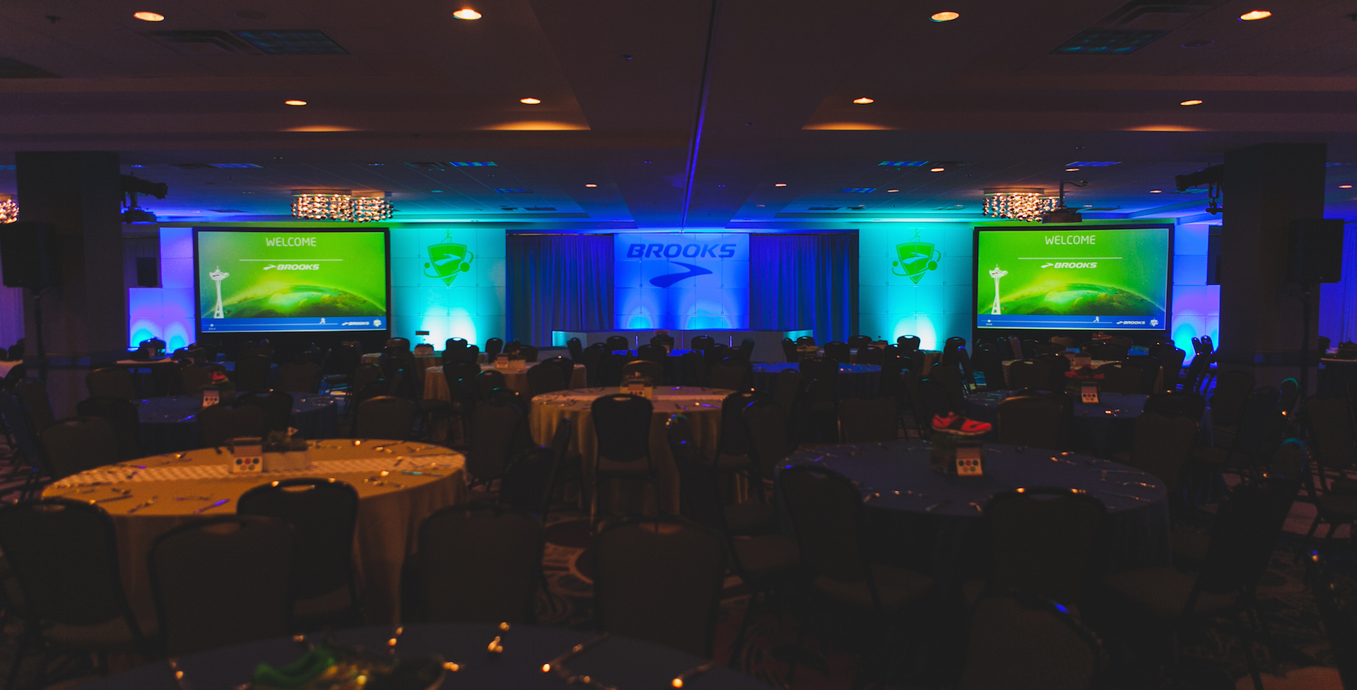 Two big screens dispalying logos are on either side of a stage for a corporate event. There is blue and green lighting and an impressive atmosphere.